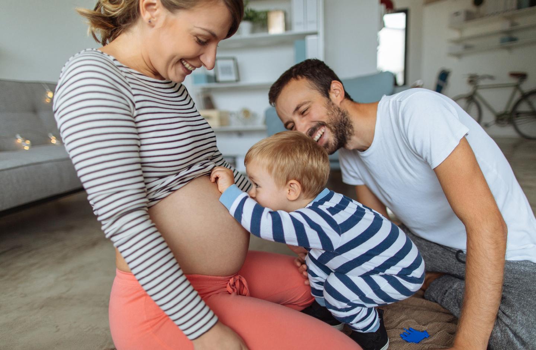 2 Jähriger guckt neugierig Mamas schwangeren Bauch an und Papa lacht.