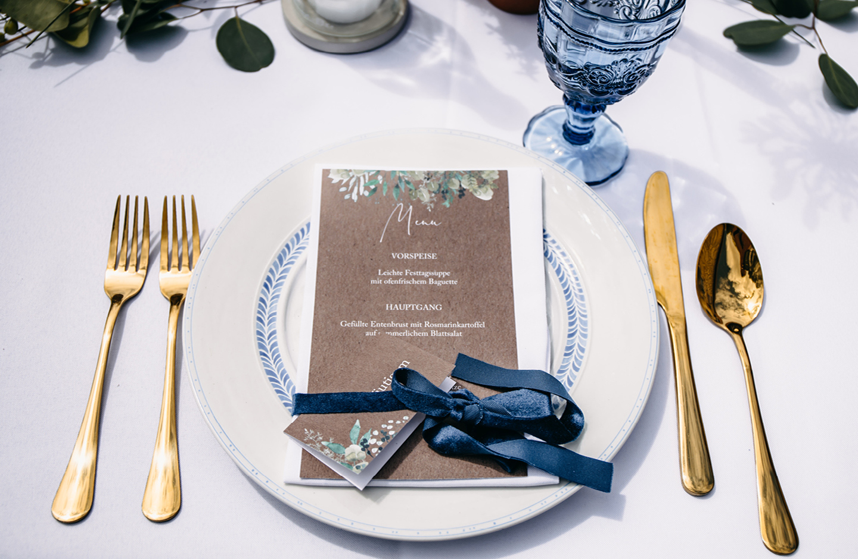 Menükarte & Namenskarte aus Kraftpapier mit Greenery Illustrationen liegen auf einem weißen Teller auf der Hochzeitstafel.