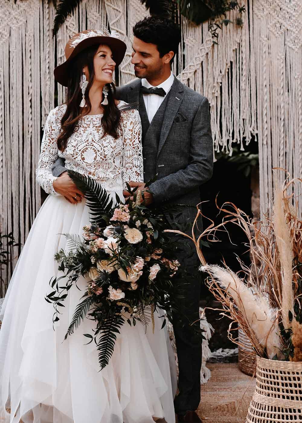 Das Brautpaar blickt sich verliebt und glücklich in die Augen und steht mit dem Brautstrauß in der Hand eng umschlungen vor der Traulocation.