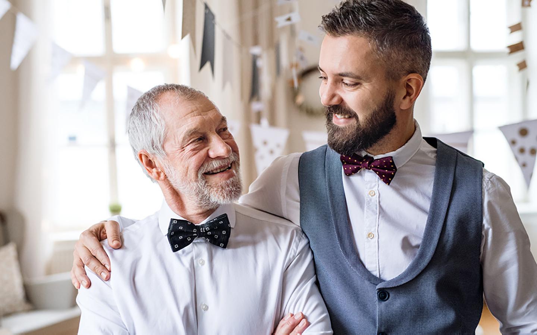 Vater und Sohn blicken sich freudig in die Augen. Sie tragen ein Hemd und einen Anzug.