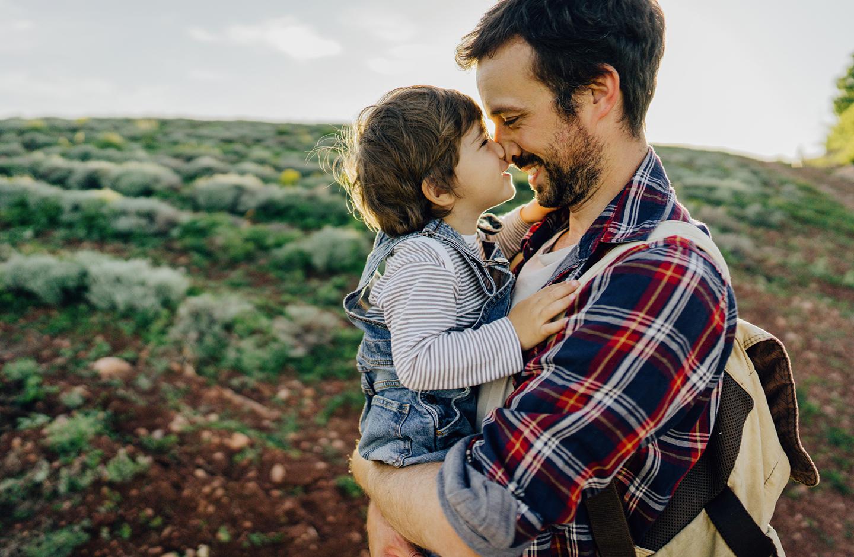Papa und Kind lachen sich draußen auf einem Feld an.