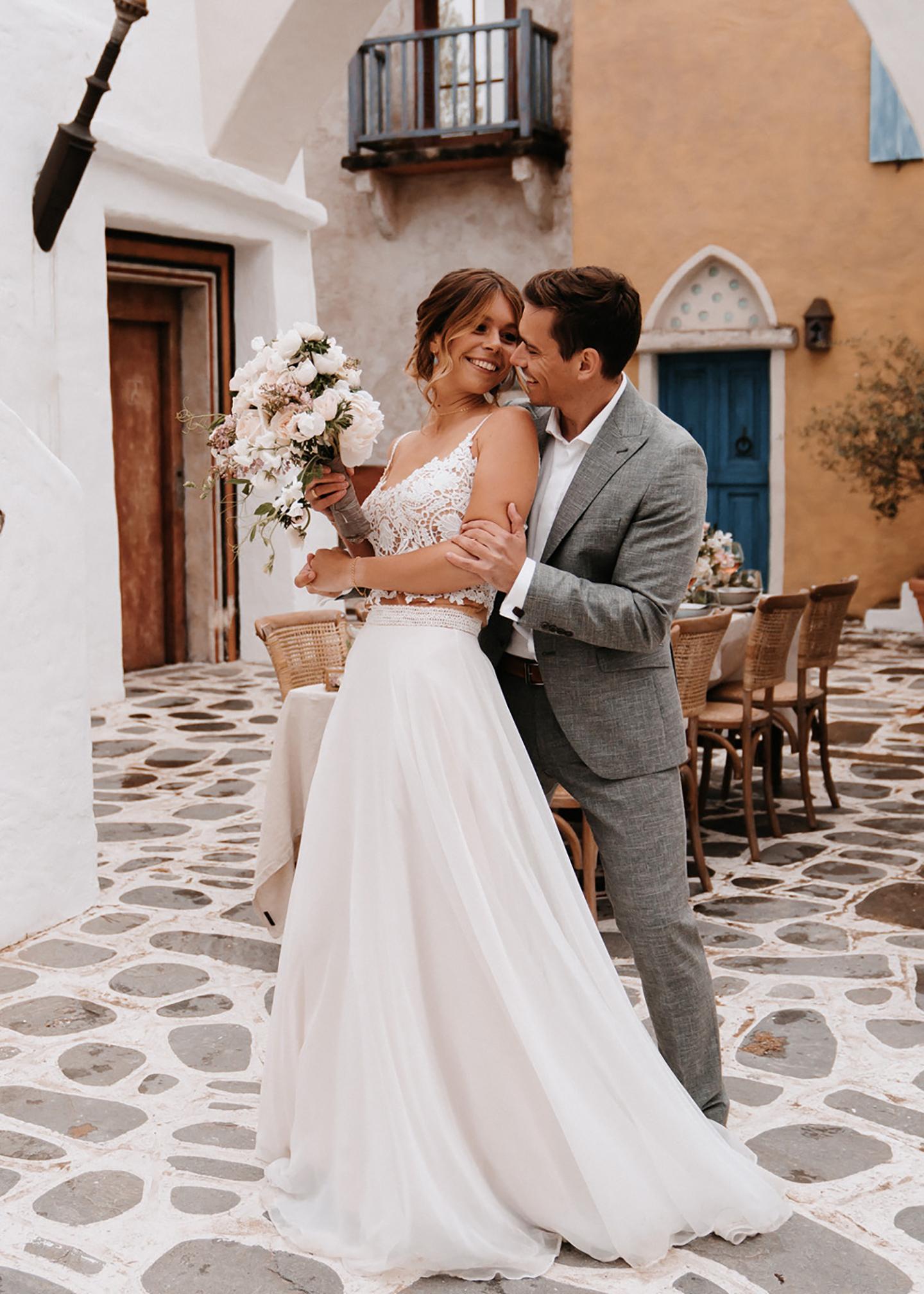 Mediterrane Hochzeit: Das Hochzeitspaar steht vor dem Hochzeitstisch und schaut sich verliebt an.