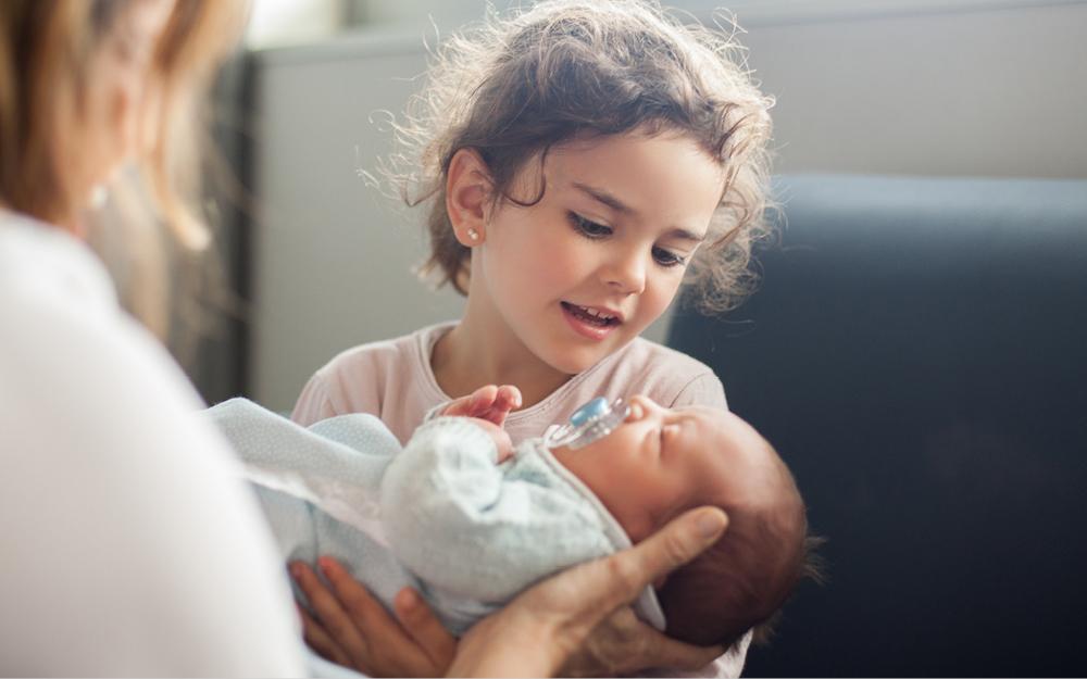 Große Schwester hält Neugeborenes