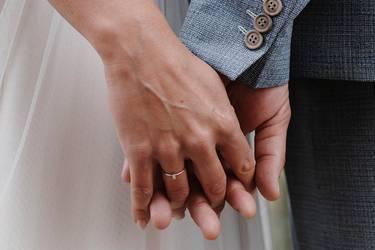 Frisch vermähltes Ehepaar hält sich an den Händen. Man sieht den Ehering am Finger der Braut.