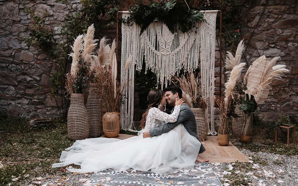 Boho-Greenery Hochzeit im Freien: Das verliebte Brautpaar wird vor der romantischen Boho Dekoration aus Pampasgras und Makramee fotografiert.