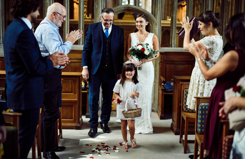 Brautvater führt die Braut durch Mittelgang der Kirche zum Altar. Ein Blumenmädchen streut Blumen und die Gäste haben sich erhoben.