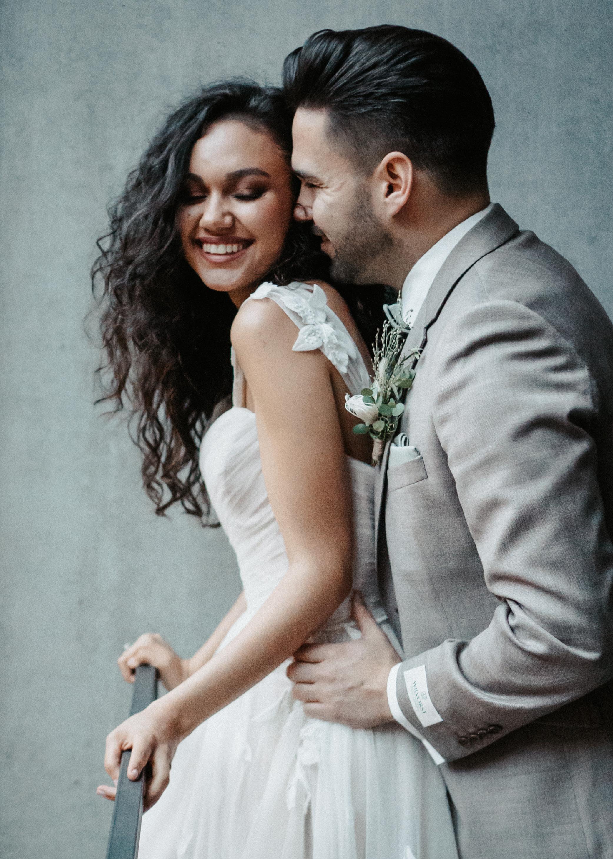 Verliebtes Brautpaar lacht sich verliebt an.