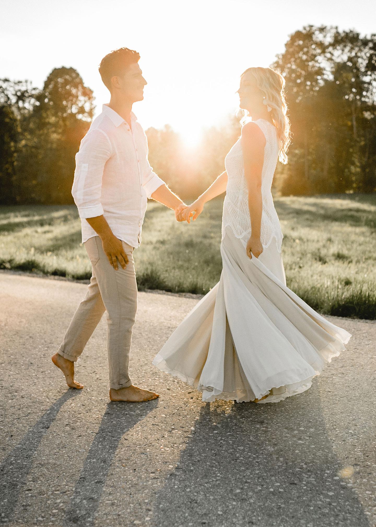 Tanzend auf der Straße bewegt sich das Brautpaar in der untergehenden Sonne.