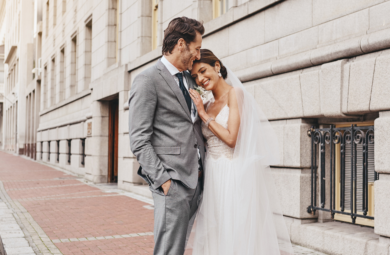 Braut lehnt glücklich an Bräutigam in grauem Anzug.