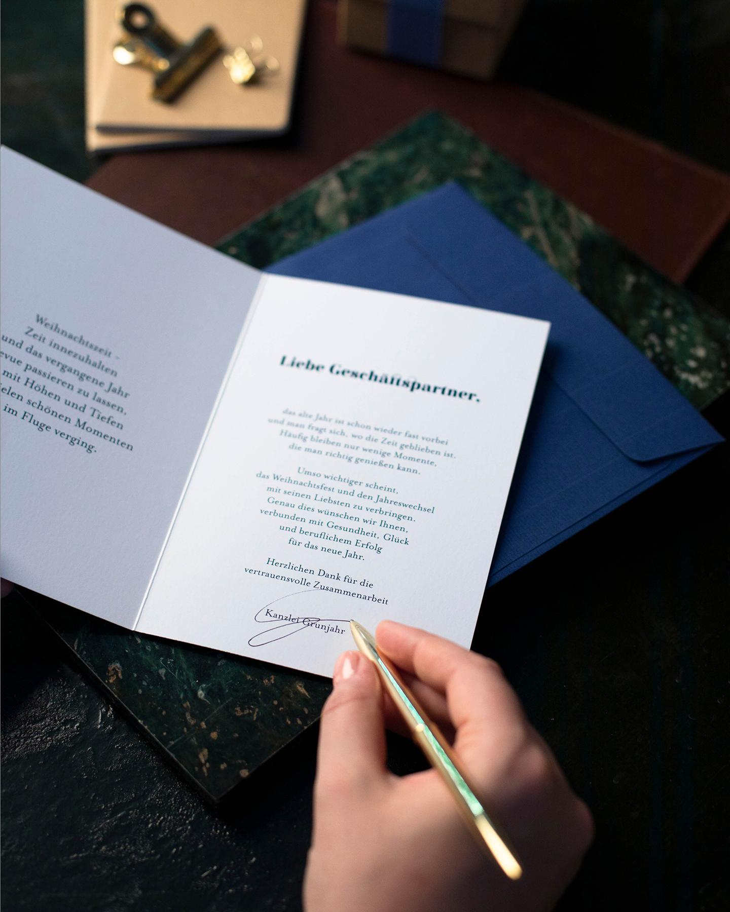 Eine Weihnachtskarte an die Geschäftspartner wird per Hand unterschrieben.