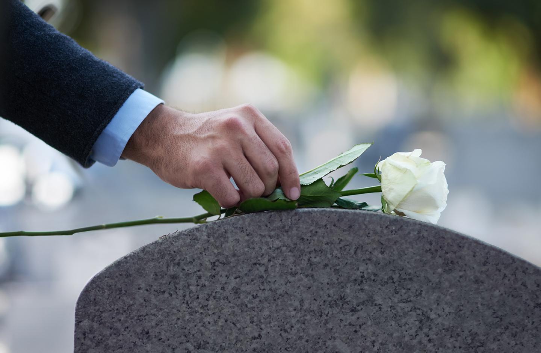 Mann legt weiße Rose auf Grab beim Trauergottesdienst.