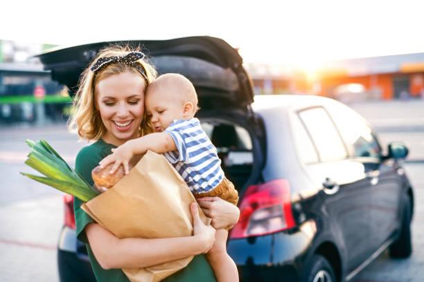 Mama mit Baby und Einkaufstüte auf dem Arm vor Auto mit geöffneter Heckklappe