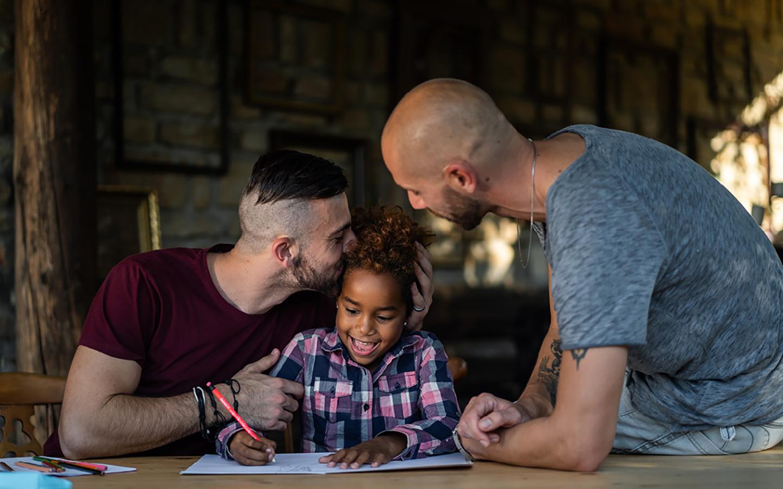 Zwei Väter sitzen mit ihrer Tochter am Tisch und unterstützen sie bei ihren Hausaufgaben.