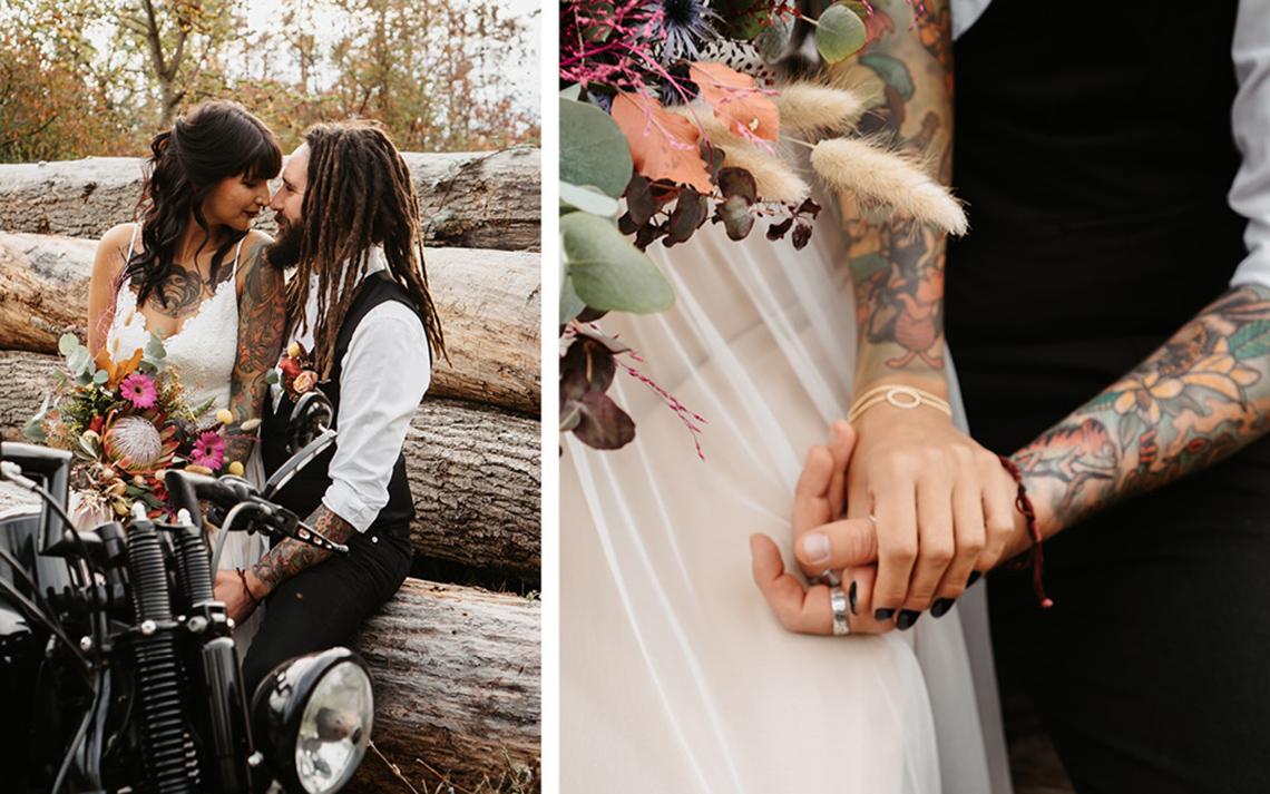 Das Brautpaar wird vor gefällten Baumstämmen in der Natur fotografiert. Die Braut hält den bunten, fröhlichen Brautstrauß in der Hand und vor ihnen steht die schwarze Harley
