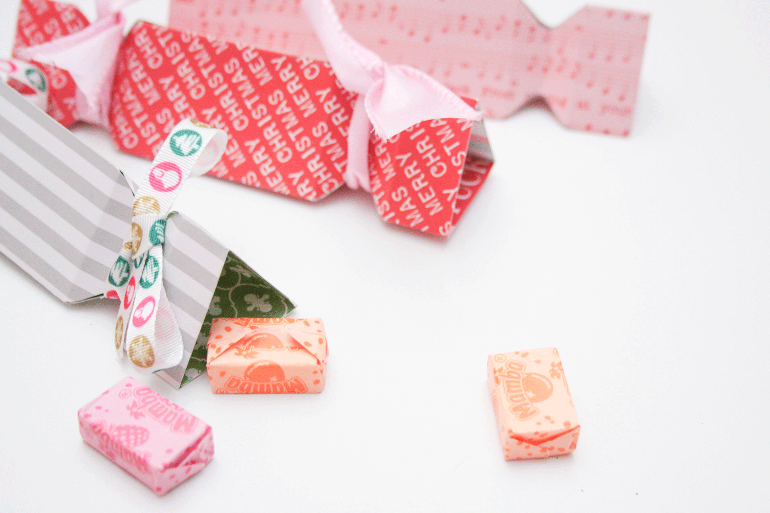 Süßigkeiten für Adventskalender werden in Bonbon-Formen aus Papier gefüllt.