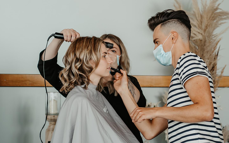 Die Braut wird von einem Team aus zwei Leuten geschminkt. Ein Mann und eine Frau kümmern sich um das Makeup und die Haare der Braut.