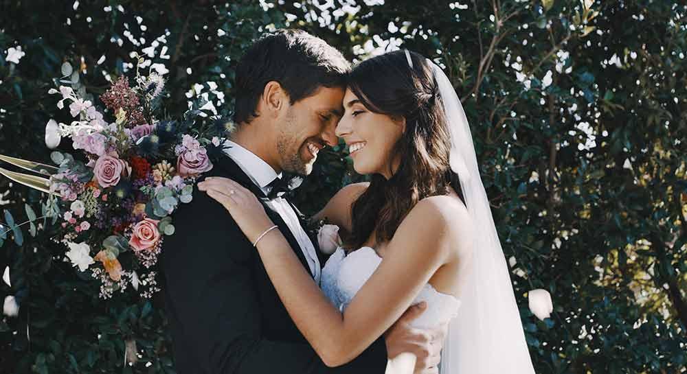 Verliebtes Brautpaar lächelt sich verliebt an.
