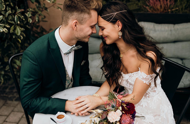 Paar sitzt am Hochzeitstag in einem Kaffee und hält Händchen.