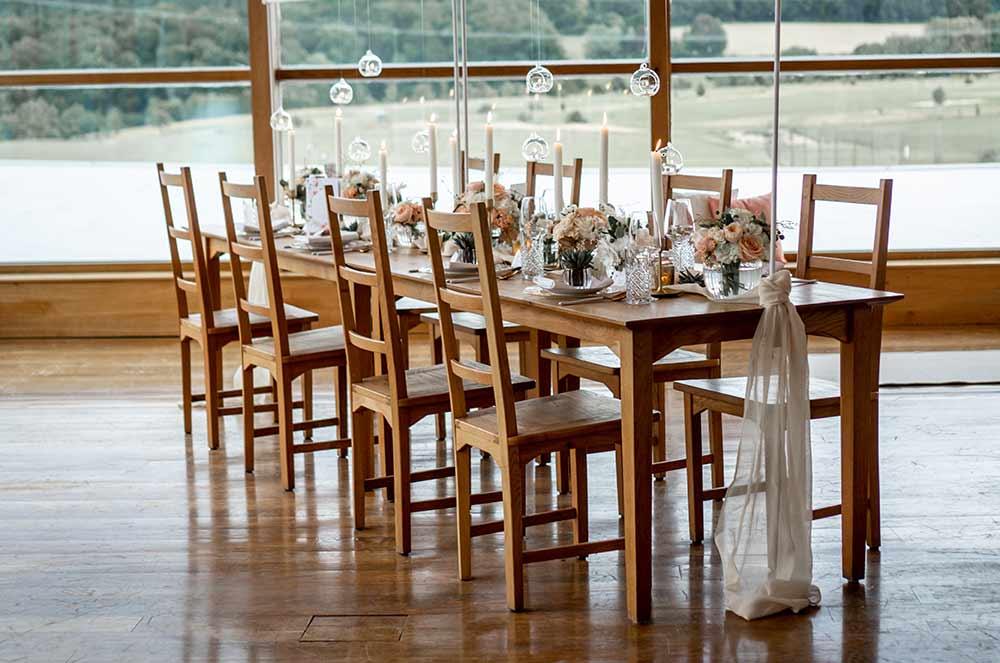 Hochzeitstafel: Ein großer Holztisch ist dekoriert mit Blumen in Koralle, weißen Kerzen und Teelichtern aus Glas.