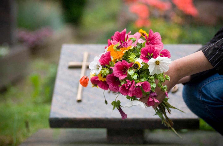 Frau legt nach dem Trauergottesdienst Blumen am Grab ab.