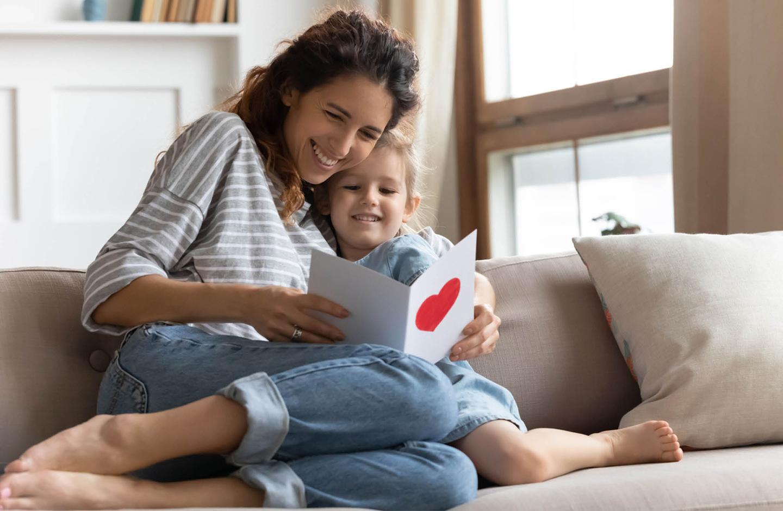 Mutter und Kind sitzen auf dem Sofa und schauen sie einen Brief an, den sie bekommen haben.