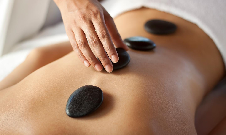 Frau plaziert heiße Steine auf Rücken