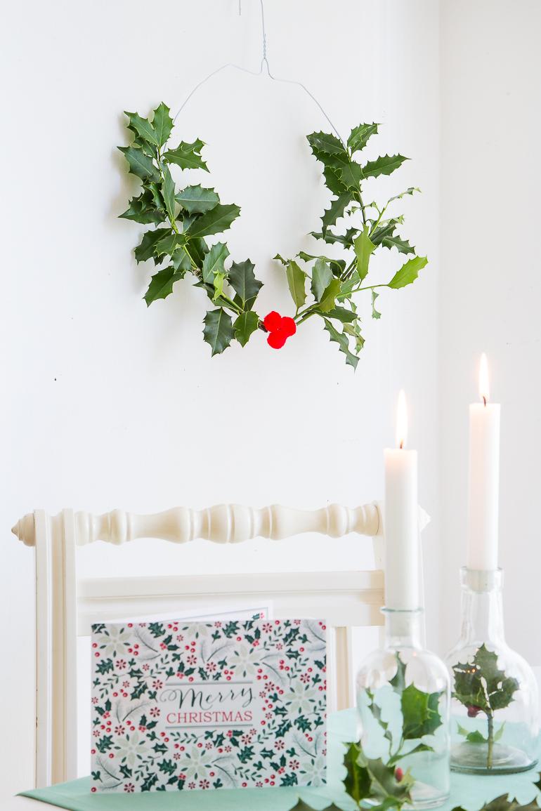 Kleine Glasflaschen mit Zweigen befüllt werden zur Weihnachtstischdeko.