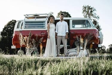 Das Brautpaar ist sitzend in einem rot-cremefarbenen Bulli zu sehen. Daneben sind Pampasgras und andere Trockenpflanzen in zauberhaften Vintage Vasen zu sehen..