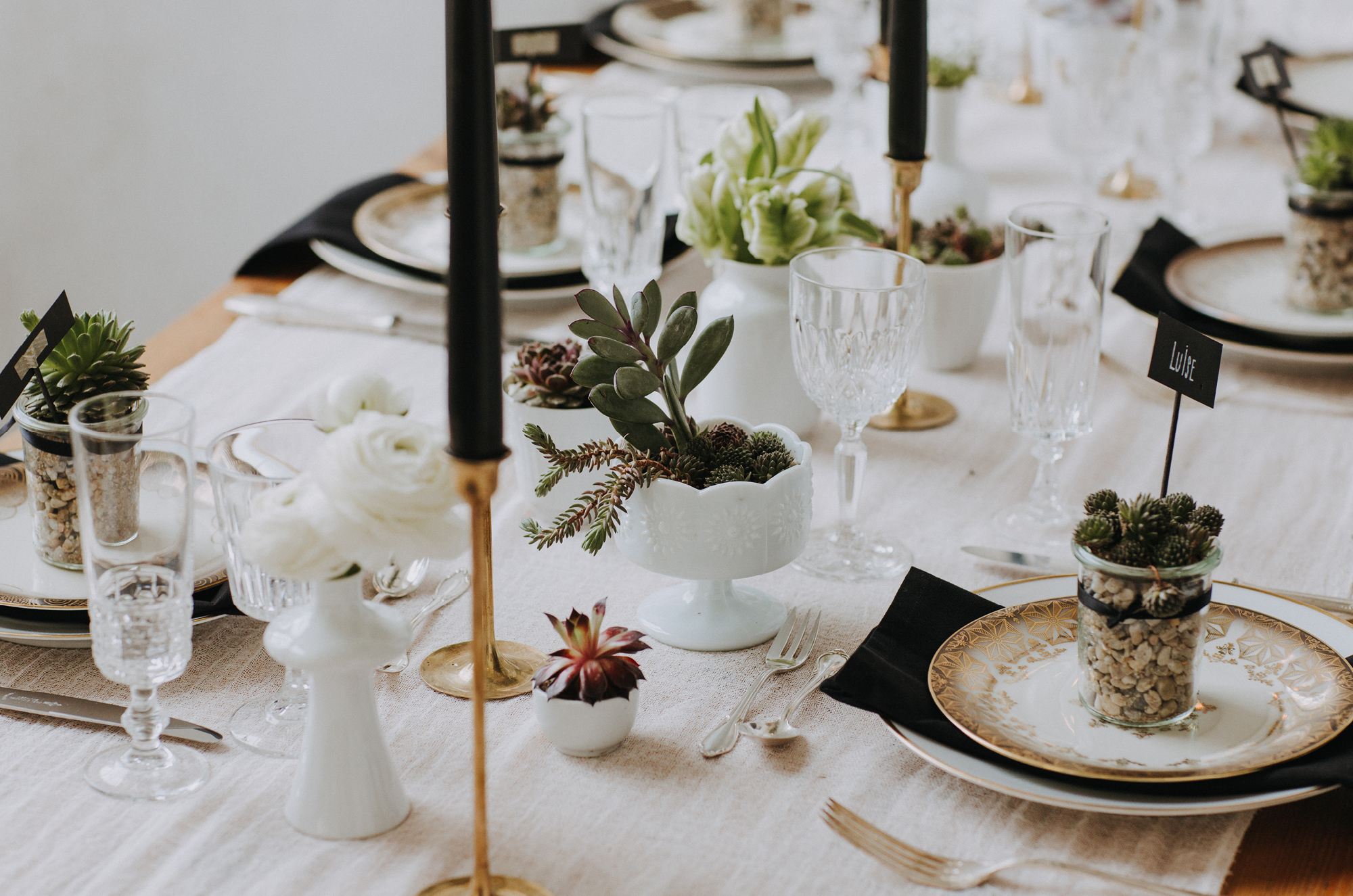 Schlichte Hochzeitstafel, die nachhaltig mit Sukkulenten und wenigen Details dekoriert wurde.