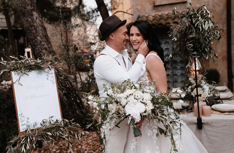 Verliebtes Brautpaar schaut sich verträumt an. Die Braut hält einen großen Boho Brautstrauß mit viel Greenery.
