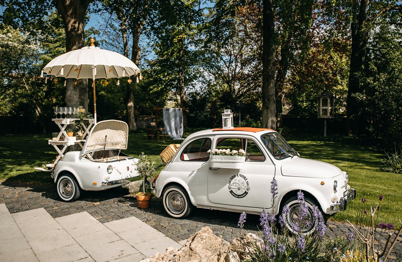 Oldtimer mit Anhänger steht auf der Terrasse am Weingut. Der umgebaute Anhänger wird als Sektkühlung genutzt.