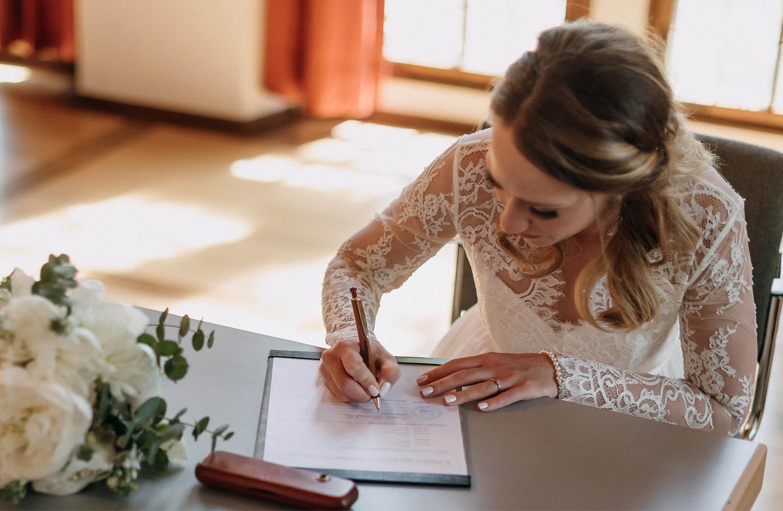 Braut unterschreibt Dokument der Eheschließung im Standesamt.