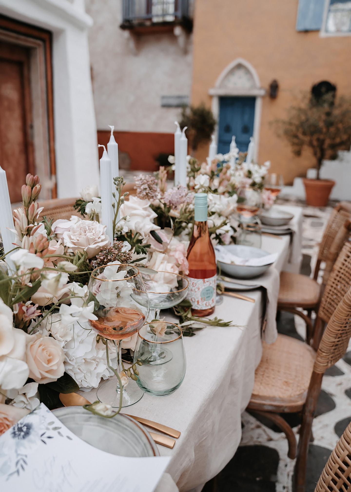 Der angerichtete mediterrane Hochzeitstisch erstrahlt mit einer Pracht aus Blumen und Dekoration. Das Besteck ist rosegold und passt zu den beige-pastellorangenen Häusern im Hintergrund.