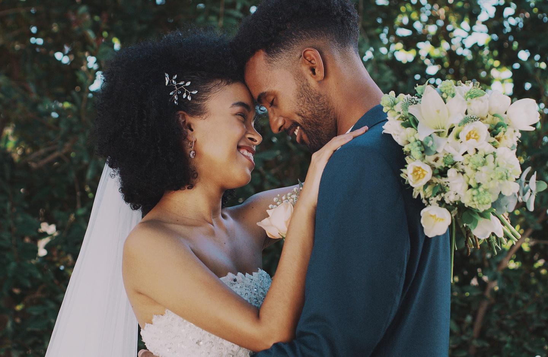 Verliebtes Hochzeitspaar schaut sich verträumt in die Augen und lacht.