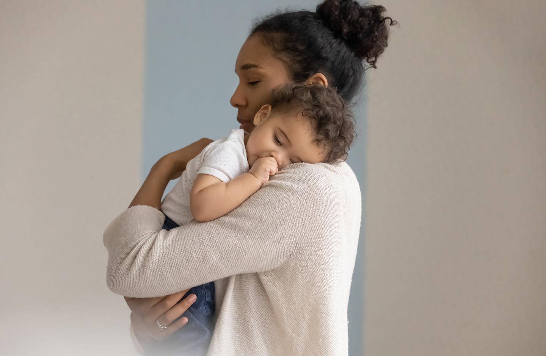 Mama betreut und kuschelt mit Baby auf dem Arm, um Baby Kosten zu sparen.