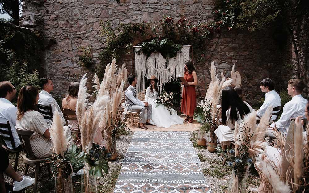Während der Trauung blickt die Braut ihrem Ehemann glücklich in die Augen. Die Gäste schauen gespannt bei der Trauung zu.