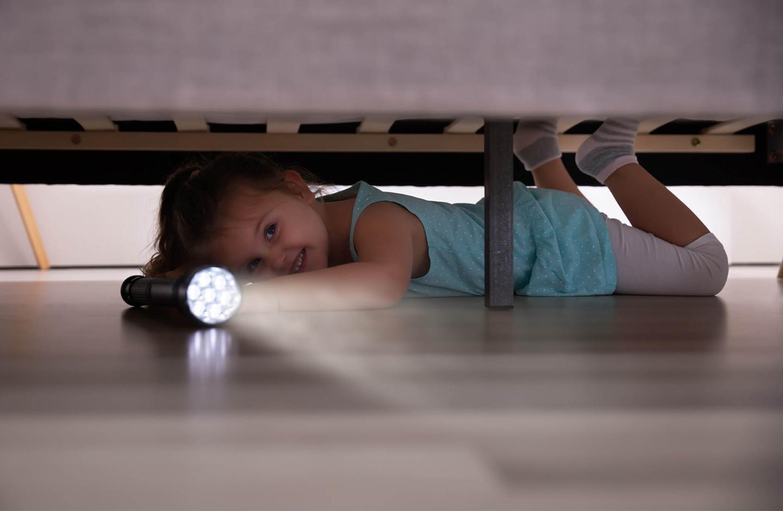 Kind leuchtet mit einer Taschenlampe unter das Bett
