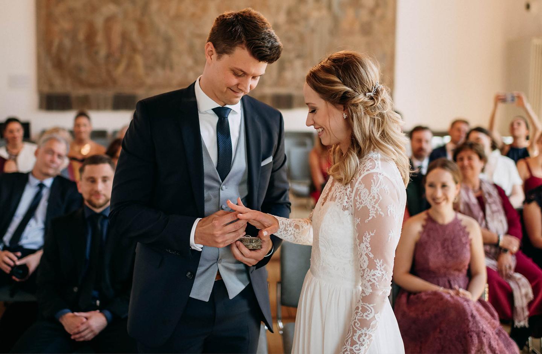 Bräutigam steckt seiner Braut nach der Eheschließung den Ring an den Finger.