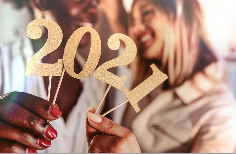 Zwei Frauen halten eine gold, glitzernde 2021, die an Holzspießen befestigt ist, in die Kamera.