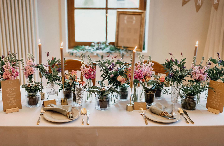 lange festlich geschmückte Hochzeitstafel mit Blumenarrangements und Kerzenleuchter