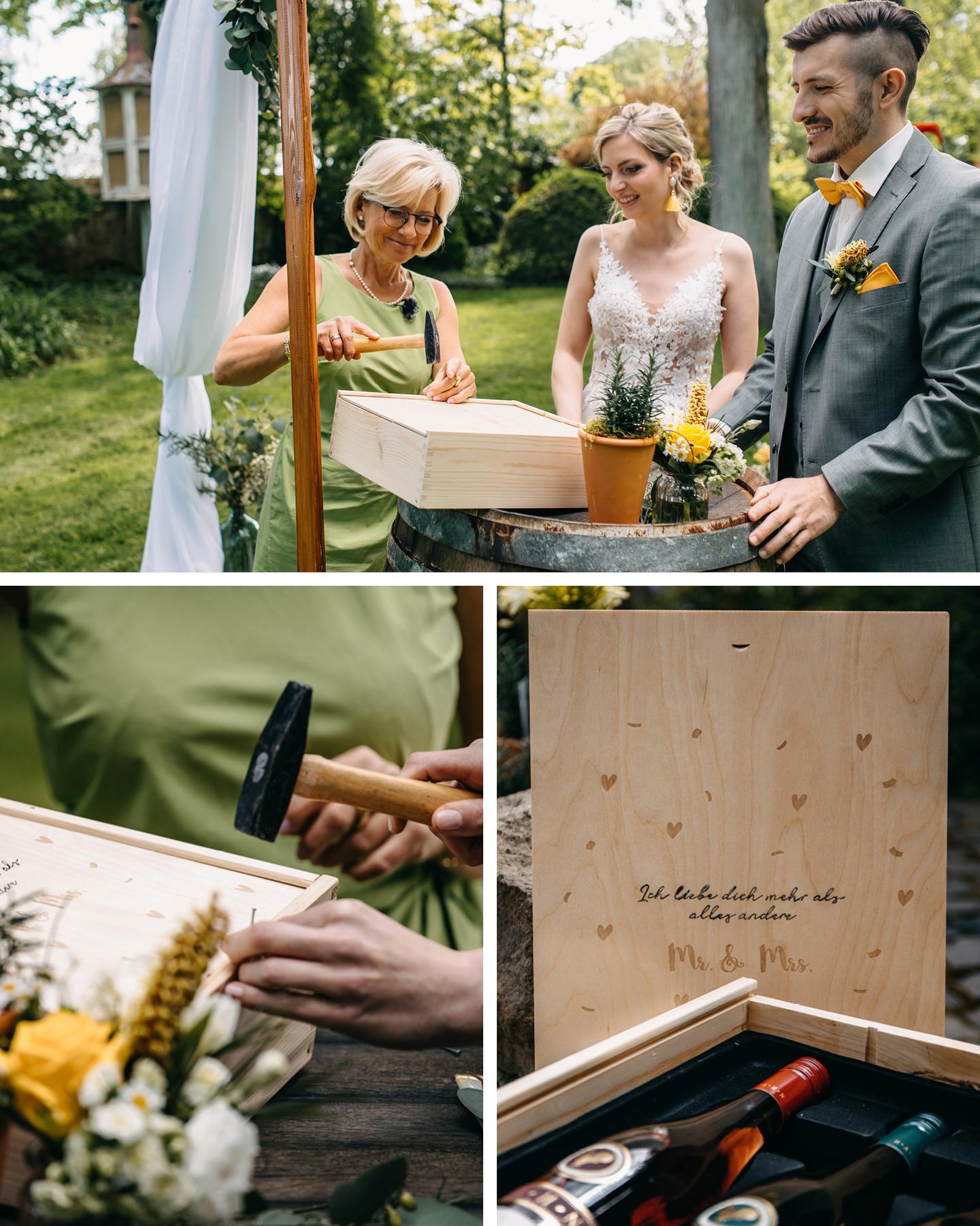 Brautpaar mit freier Traurednerin verschließen Holzkiste mit Wein und guten Wünschen zum 1. Hochzeitstag.