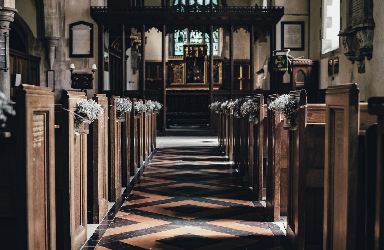 Festliche Kirche mit Holzbänken ist mit Blumenschmuck in Weiß dekoriert.