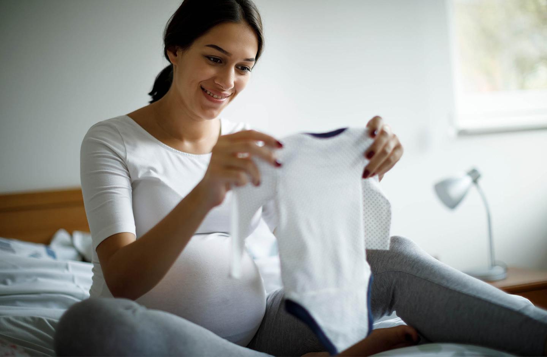 Schwangere Frau sitzt auf dem Bett und hält ein Babystrampler in den Händen
