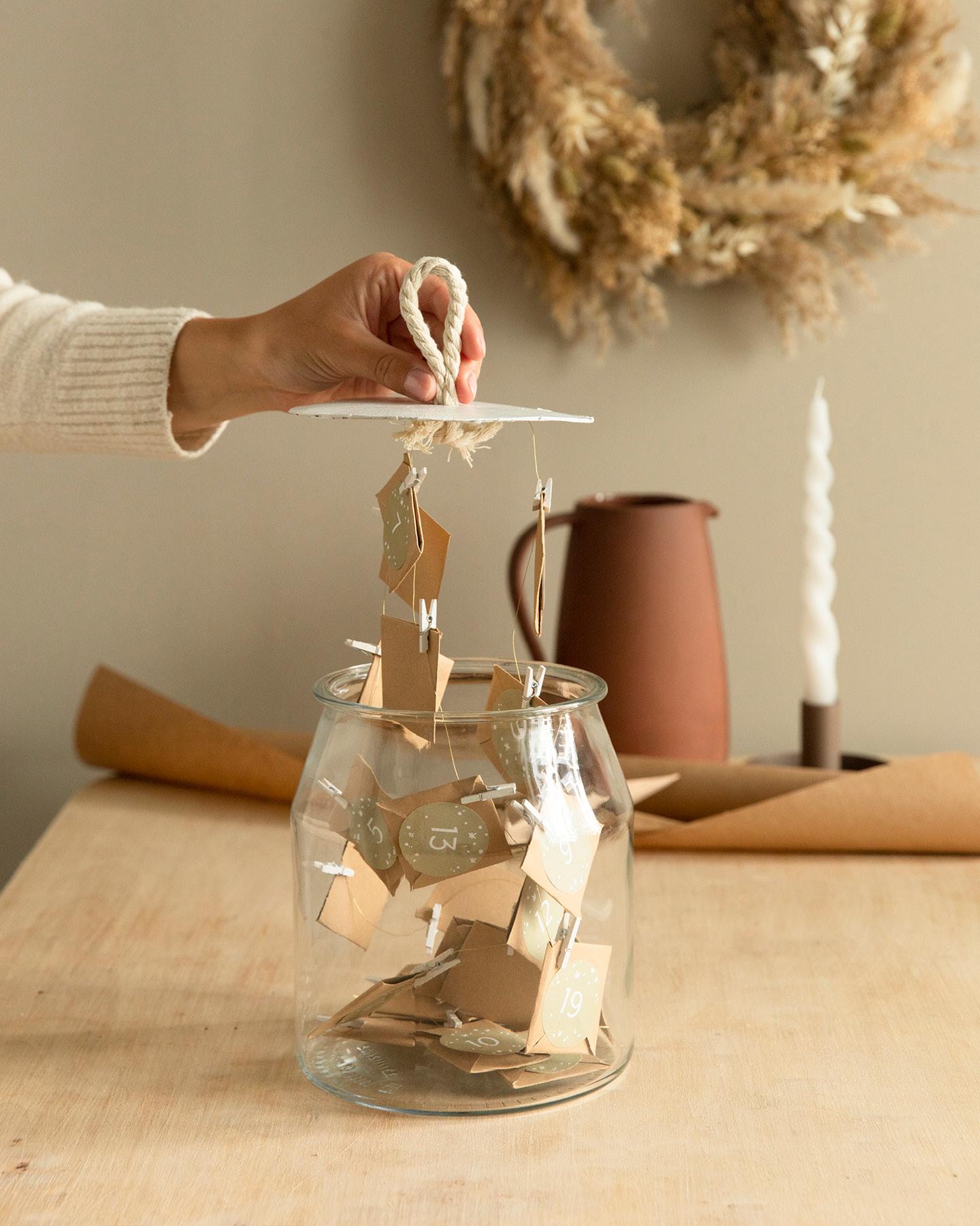 Frau hält Deckel aus Pappe an einer Schlaufe fest, an dem kleine Gutscheine aus Papier befestigt sind als Adventskalender.