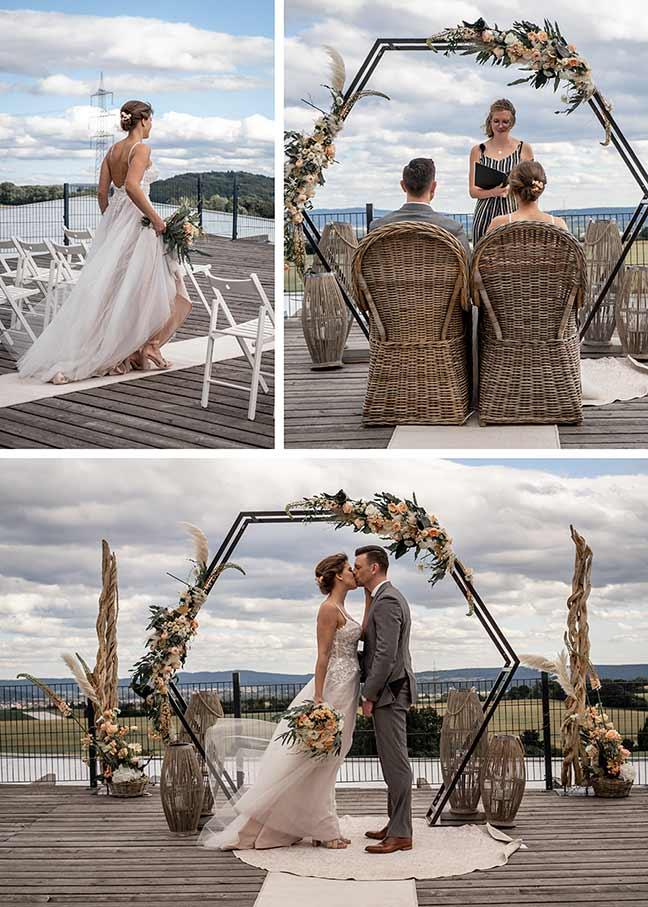 Freie Boho Trauung unter freiem Himmel. Brautpaar küsst sich verliebt.