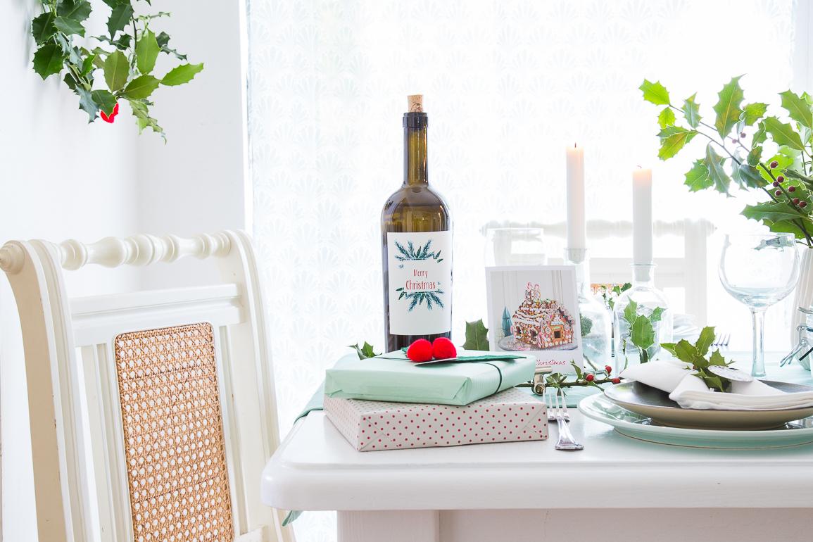 Tischdekoration zu Weihnachten mit mintgrüner Tischdecke, grünen Zweigen und Weihnachtsfotos.