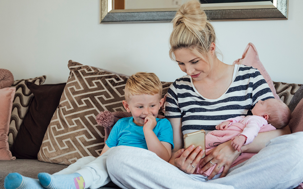 Mutter sitzt mit zwei Kindern auf dem Sofa