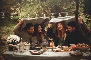 Freunde sitzen am gedeckten Tisch im Garten. Über ihren Köpfen halten sie eine Decke, um sich vor dem Regen zu schützen.