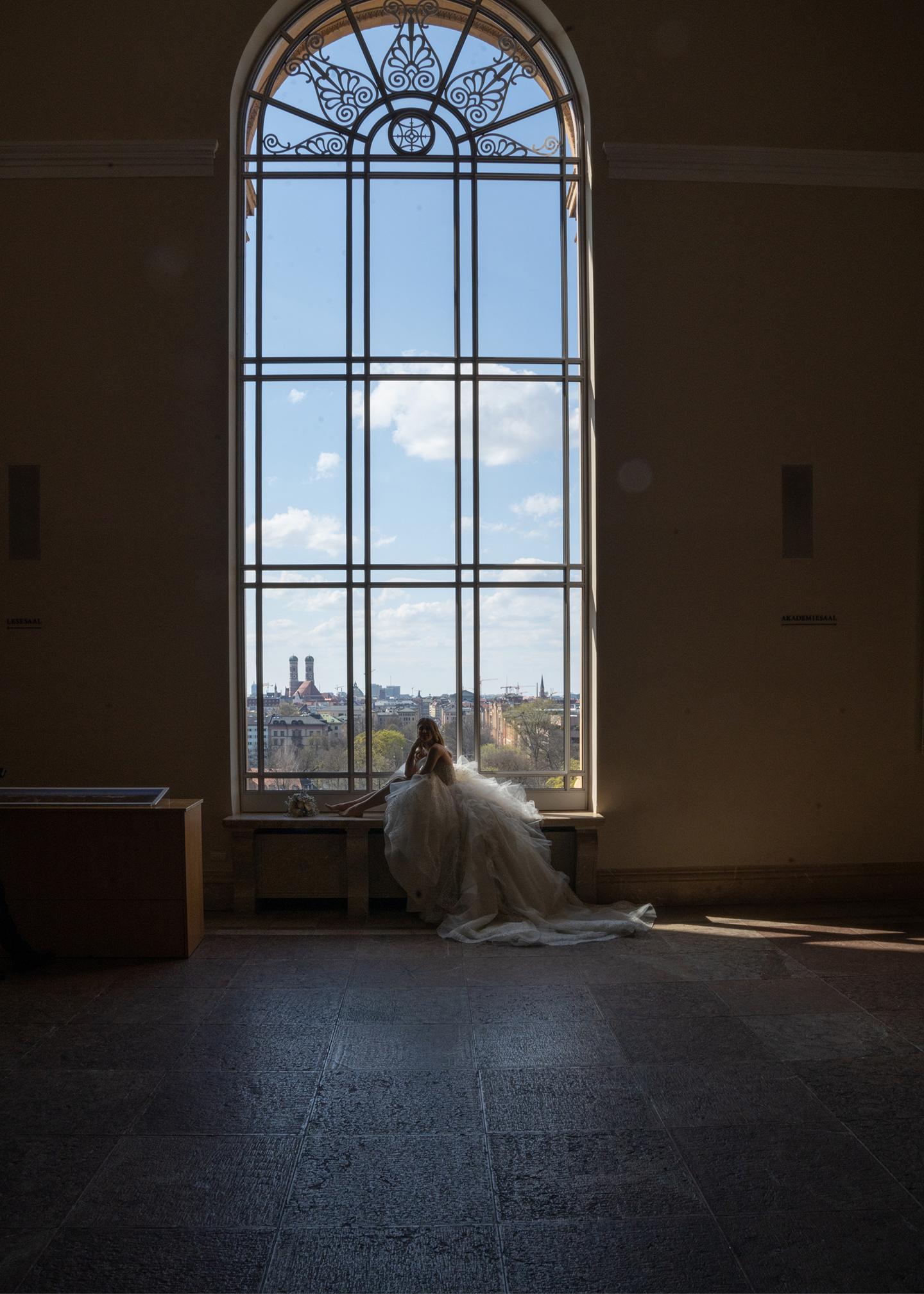 Die Braut posiert in der atemberaubenden Location vor einem riesigen, mit vielen Details versehenen Fenster.