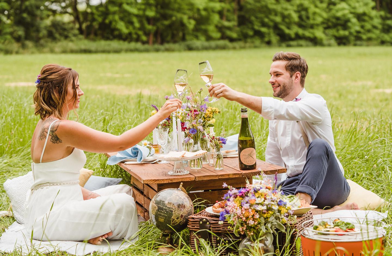 Hochzeitspaart stößt mit Sekt am Picknicktisch auf einer Wiese auf ihre Hochzeit an.